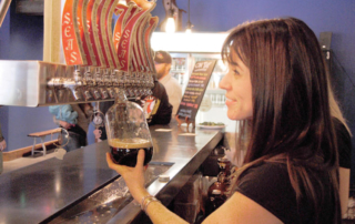 Bartender pouring a dark beer.