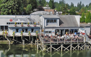 Exterior of Tides Tavern with people sitting on the outdoor deck.