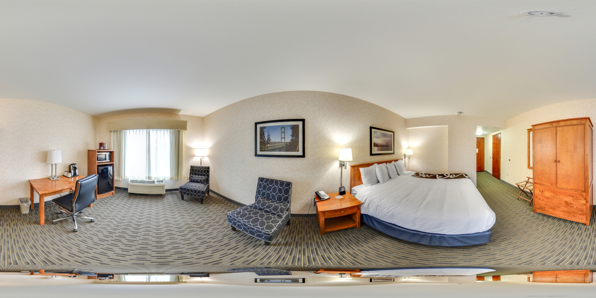 Panorama view of hotel room with king bed.
